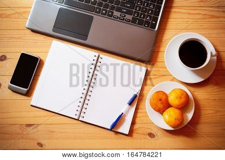 Overhead view of notebook laptop smartphone fresh cakes and white cup of coffee on rustic wooden background