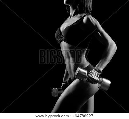 Her body is her best project. Cropped black and white shot of a fit strong muscular woman working out with weights