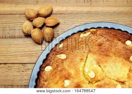 Unshelled Almond Nuts Next To A Freshly Baked Frangipane Tart Or Cake