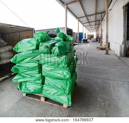 A stack of green sacks on a pallet. Loading Dock Industrial cargo warehouse.