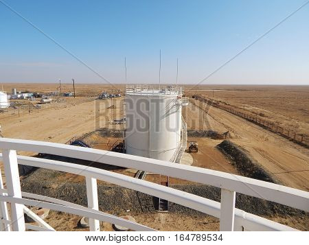 Vertical steel tanks. View from the top of the stairs.