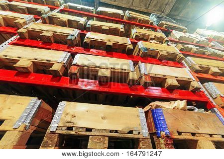 Industrial warehouse. A set of wooden boxes lie on metal racks.