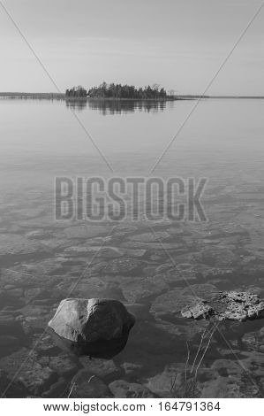 Dead calm afternoon image of shallow and clear lake huron water and limestone rocks along theshoreline. A small tree-covered island is on the horizon. Overall feeling is a calm peaceful tranquil serene and wild background in this black and white capture.