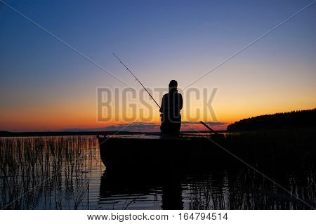 The picture shows a silhouette of a fisherman. Fisherman stands in the boat and catches a fish.