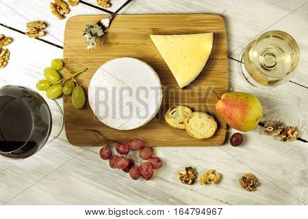 A photo of a tasting with two glasses of wine, red and white, different types of cheese, bread, nuts, pear, grapes, on a wooden board