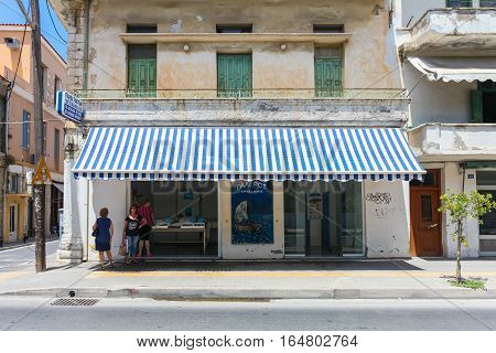 Rethymnon, Island Crete, Greece - July 1 2016: Local citizens are speaking with each other near fish store with fresh seafood