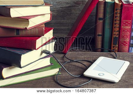 ebook and old books on wooden table. tablet download information from many books. new technology concept. vintage toning