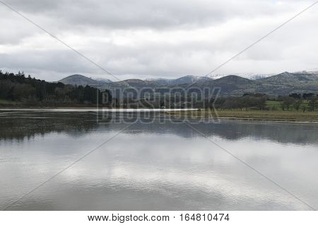 Snow capped mountains behind a tranquil river with beautiful reflection of the mountain range in the water