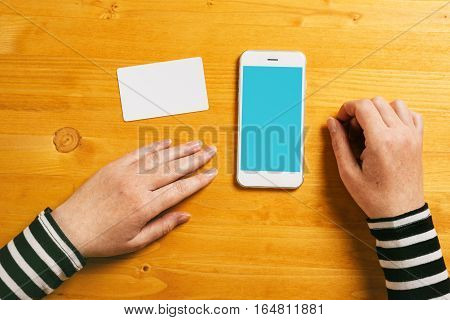 Top view mock up of female hands with mobile smart phone and blank business card as copy space for online shopping new technology electronic payment internet activity e-business concept