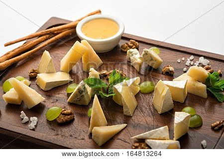 A set of cheese snacks. On a wooden stand. The sauce, crackers.