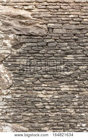 Textures and patterns concept. Detailed closeup background wall made of grey stone rocks.