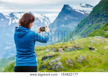 Tourism vacation and travel. Female tourist taking photo with camera enjoying scenic summer mountains landscape Norway Scandinavia.