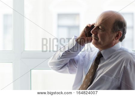Elderly man sitting on a windowsill and read news on your smart-phone. Rest in the middle of the working day.