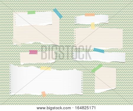 White, light brown, note, notebook, copybook paper strips and sheets stuck with sticky tape ongreen wavy pattern.