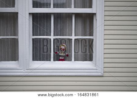 Christmas rag doll looking out the window