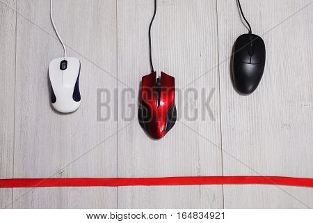 Interactive race on speed between the red white and black computer mouse on a wooden gray background. The input device for cursor control. Competition computing devices. Red ribbon