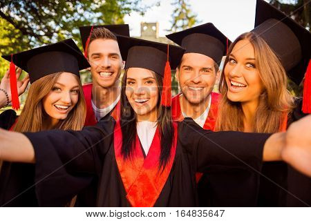 Excited Five Successful Happy Five Graduates In Robes And Hats With Tassel Together Making Selfie Ph