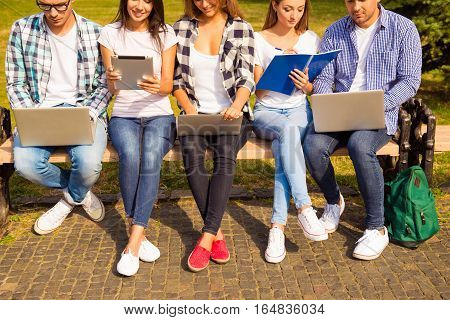 Close Up Photo Of Happy Diverse Classmates Sitting On Bench And Studying