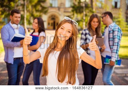 Excited Happy Girl Standing Near University And Her Friends And Showing Thumb-up