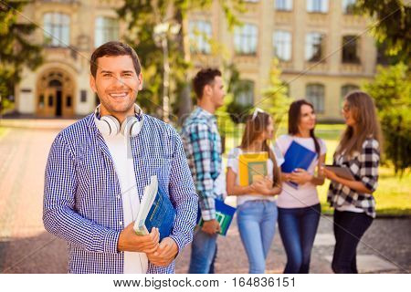 Happy Young Man Holding Books While Standing University Background
