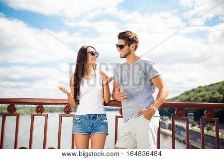 Young couple on the bridge having fun and smiling on weekend