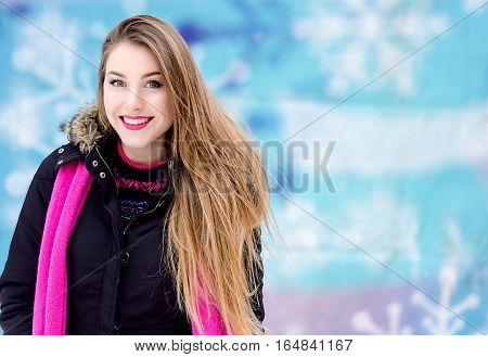 Young lady with long blonde hair and perfect makeup looking at the camera and smiling, outdoor shooting in the city. Winter look in stylish clothes. Close up portrait in blue background with snowflake