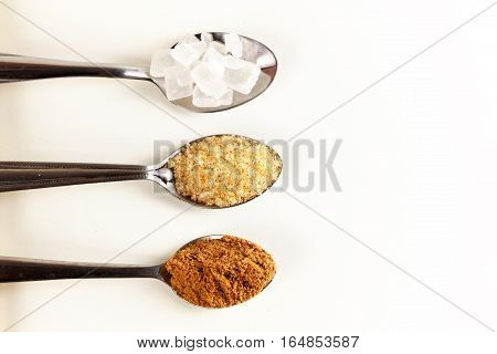 Brown cane sugar in a metal spoon on the white background. Pure cane sugar for natural. no additives.