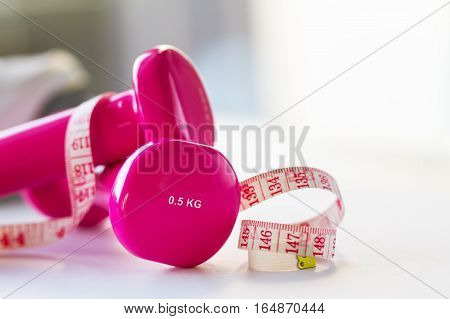 Pair of pink fitness dumbbells with centimeter ribbon on bright shiny background. Horizontal with copy space.