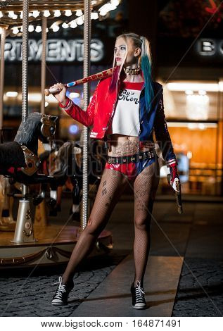 Cosplayer girl in costume Harley on background lights of night city. Cosplay