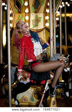 Smiling cosplayer girl in costume Harley on background lights of carousel ride. Cosplay