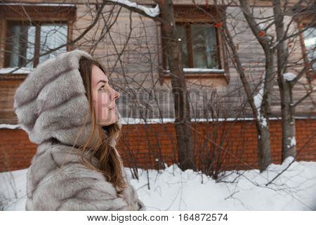 walk around the city: the girl's portrait in a profile at a small lodge in winter