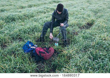 Hiker Sitting On Stool In Field Preparing Camping Gas Fire.