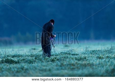 Hiker Unfolding Stool In Wet Meadow. Noordijkerveld. Achterhoek. Gelderland. The Netherlands.