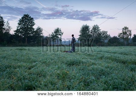 Man Standing With Stool And Backpack In Meadow At Dawn. Noordijkerveld. Achterhoek. Gelderland. The