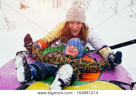 Happy smiling mother and child sitting on snow tube. Young woman and little boy have fun and sliding down. Winter vacation concept.