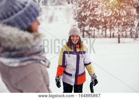 Portrait of young smiling woman having fun on snow hill. Winter vacation concept.