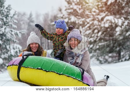 Happy smiling caucasian women and child having fun on snow tubing. Winter vacation.