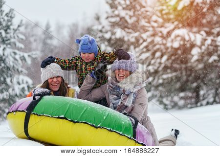 Winter vacation: group of people sledding on snow tubing. Two women and little kid having fun outdoors.