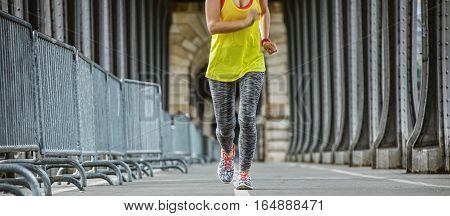 Outdoors fitness in Paris. Closeup on young sportswoman running on Pont de Bir-Hakeim bridge in Paris