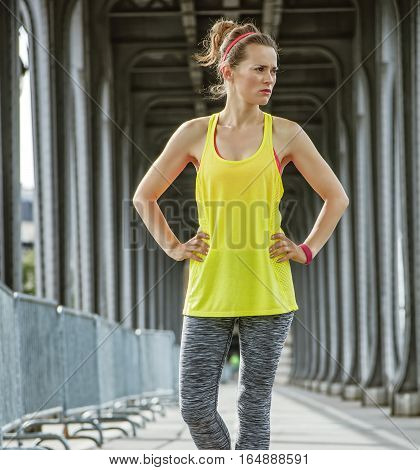 Outdoors fitness in Paris. Portrait of young active woman standing on Pont de Bir-Hakeim bridge in Paris