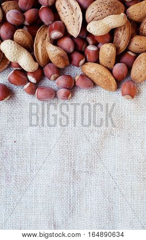 Nuts hazelnuts peanuts almonds on sacking. Background of canvas fabric and nuts.