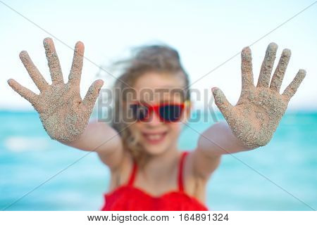 Summer vacation concept. Smiling girl showing hands in the sand.