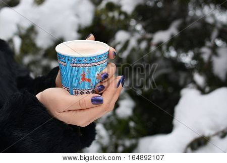 The girl in a black fur coat keeps the coffee in the cold winter forest with snow. Deer. Warm. Manicure
