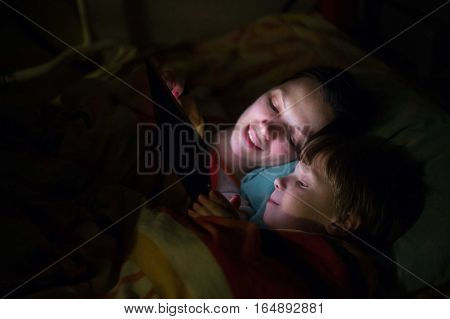 Mother and son playing on tablet, smiling, laying on bed.
