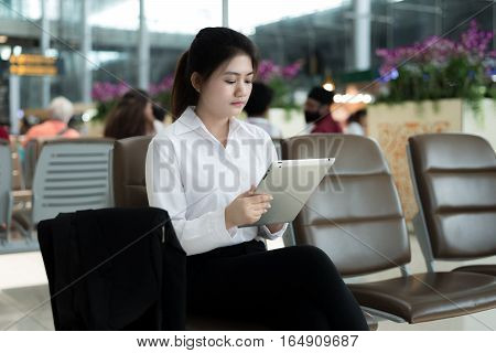 Asian young woman passenger at airport using her tablet computer while waiting for her flight in terminal at airport.