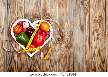 Sport and diet. Vegetables, centimeter. Peppers, tomatoes, garlic, onions, and radishes in the heart on rustic background