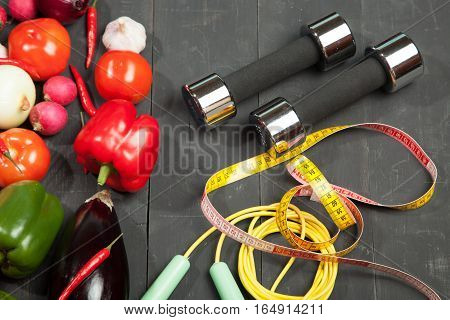 Sport and diet. Healthy lifestyle. Vegetables, dumbbells. Peppers, tomatoes, garlic, onion and radish on a black background