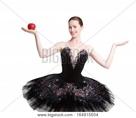Graceful ballet dancer shows apple and something in another, empty hand, isolated on white background. Ballerine in black swan dress. Slimming and weight loss concept, copy space