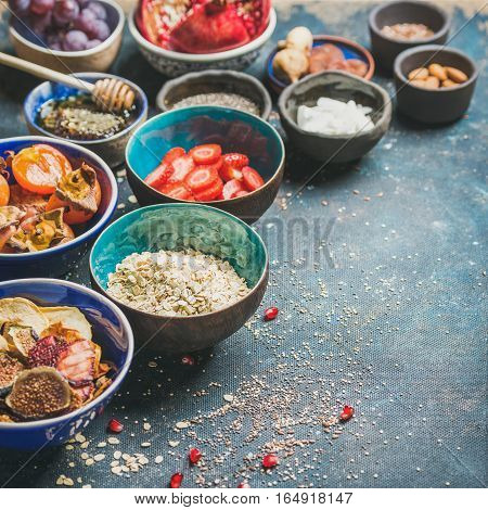 Ingredients for healthy breakfast over dark blue background, selective focus, copy space, square crop. Fresh and dried fruit, chia seeds, oatmeal, almonds, honey. Clean eating, vegan, dieting concept