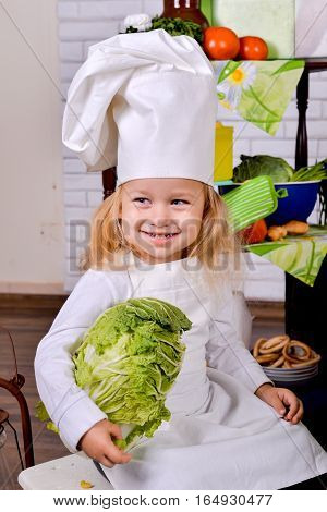 Portrait of a pretty little girl in cook clothes on a kitchen, a Chinese cabbage in hands
